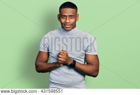 Young black man wearing casual t shirt with hands together and crossed fingers smiling relaxed and cheerful. success and optimistic