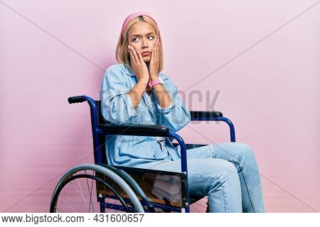 Beautiful blonde woman sitting on wheelchair tired hands covering face, depression and sadness, upset and irritated for problem