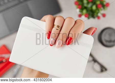 Womans Hand With Trendy Manicure Holding Notepad Over Table. Manicure Design Trends