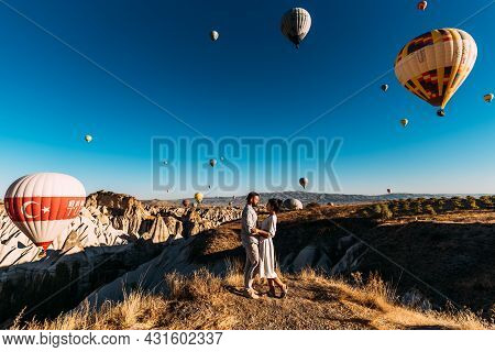 Early Morning In Cappadocia, The Flight Of Balloons. Couple Travels The World. Honeymoon Trip. Touri