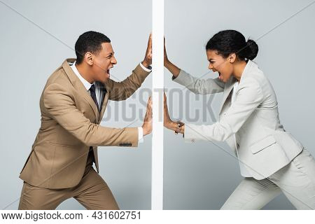 Irritated African American Businessman And Businesswoman Pulling Wall And Screaming On Grey, Gender