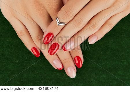 Womans Hands With Red Modern Manicure Over Green Background. Manicure Design Trends.