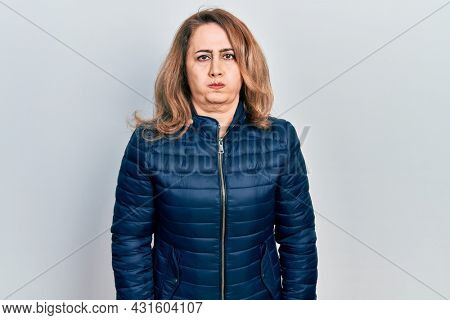 Middle age caucasian woman wearing casual clothes puffing cheeks with funny face. mouth inflated with air, crazy expression.