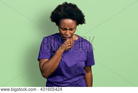 African american woman with afro hair wearing casual purple t shirt feeling unwell and coughing as symptom for cold or bronchitis. health care concept.