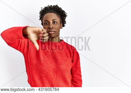 Young african american woman wearing casual clothes over isolated background looking unhappy and angry showing rejection and negative with thumbs down gesture. bad expression.