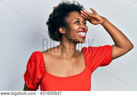 Young african american woman wearing casual clothes very happy and smiling looking far away with hand over head. searching concept.
