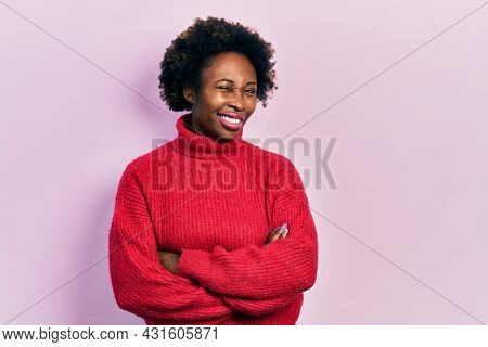Young african american woman with arms crossed gesture winking looking at the camera with sexy expression, cheerful and happy face.