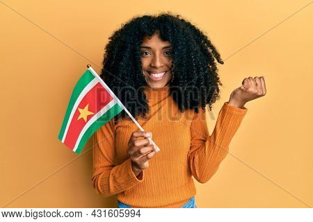 African american woman with afro hair holding suriname flag screaming proud, celebrating victory and success very excited with raised arm