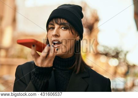 Young hispanic woman smiling happy sending audio message using smartphone at the city.