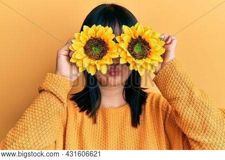 Young hispanic woman holding sunflowers over eyes puffing cheeks with funny face. mouth inflated with air, catching air.
