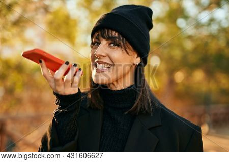 Young hispanic woman smiling happy sending audio message using smartphone at the park.