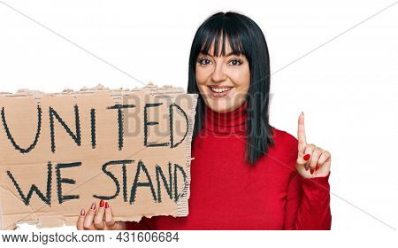 Young hispanic woman holding united we stand banner surprised with an idea or question pointing finger with happy face, number one