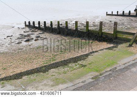 Beach Scene Showing Two Old Wooden Breakwaters And Seaweed On Seashore