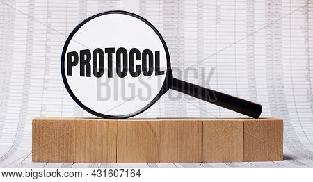Against The Background Of Reports On Wooden Cubes - A Magnifying Glass With The Text Protocol. Busin