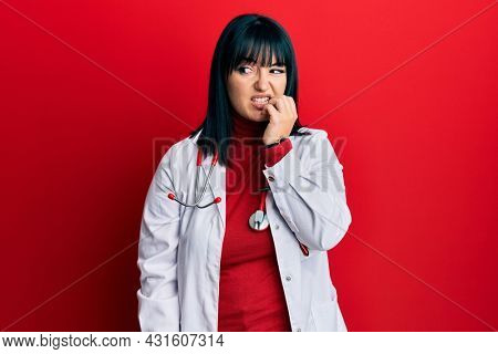 Young hispanic woman wearing doctor uniform and stethoscope looking stressed and nervous with hands on mouth biting nails. anxiety problem.