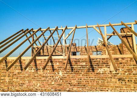 Unfinished Brick House With Wooden Roof Structure Under Construction.