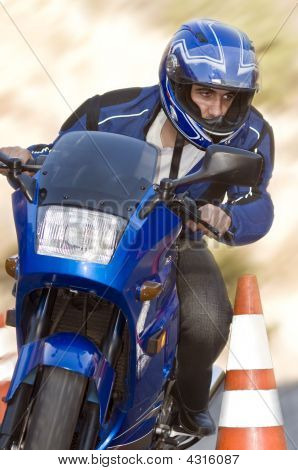 Man Passing Safety Cone On His Motorcycle