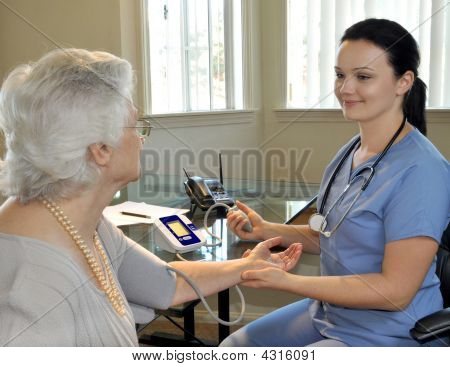 Young Nurse Measuring The Patient's Blood Pressure