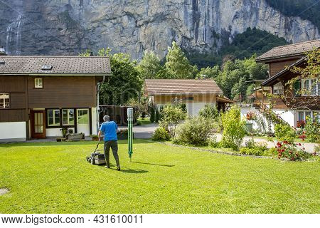 Switzerland, Wendeplatz, August 2021 - Active Elderly Male Gardener Mow Grass With Lawn Mower Agains