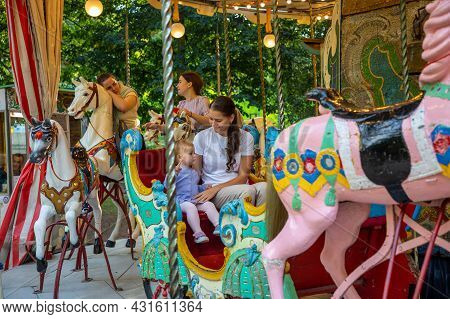 Prague, Czech Republic - 23.08.2021: Cute Baby Girl With Mother On The Horse Of Old Retro Carousel,