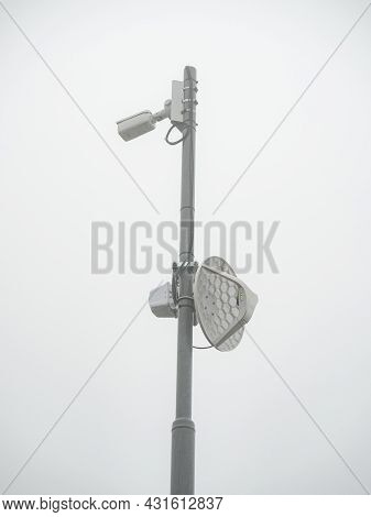 Surveillance Security Camera And Internet Satellite Parabola On Cloudy Sky As Background