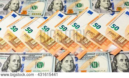50 Euros And 100 Dollars Lie In A Row, Banknotes Of Euro And Dollars On A Black Background.