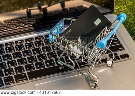 A Credit Card In A Mini Supermarket Trolley On A Laptop Keyboard. E-commerce And Online Shopping Con