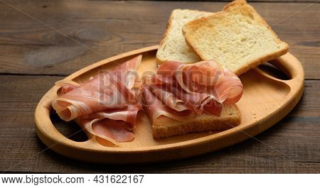 Sandwich With A White Square Slice Of Bread And Slices Of Prosciutto On A Wood Board