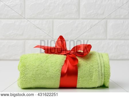 Rolled Up Terry Green Towel Tied With Red Silk Ribbon On White Shelf In Bathroom, Close Up