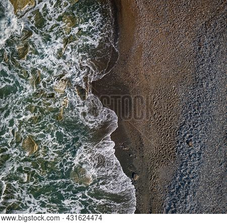 Green Waves With White Sea Foam Over Dark Sandy Shore Of Chocolate Color, Top View Texture