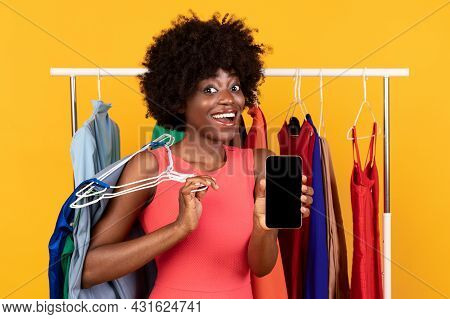 Excited African American Shopaholic Woman Showing Phone Screen, Yellow Background