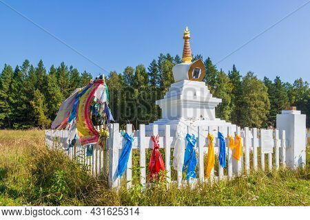 White Buddhist Stupa Of An Enlightenment Decorated With Colorful Tibetan Buddhist Prayer Scarves Wit