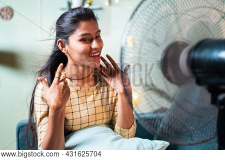 Happy Smiling Indian Woman Enjoying Fan Air During To Heat Stroke While Sitting On Couch - Concept O