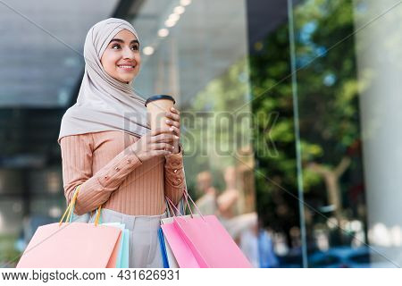 Smiling Attractive Young Arabian Female In Hijab With A Lot Of Bags With Purchases And Cup Of Coffee