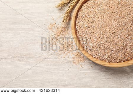 Bowl Of Wheat Bran On White Wooden Table, Flat Lay. Space For Text