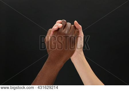 Woman And African American Man Clasping Hands On Black Background, Closeup