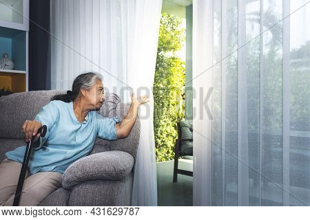 Asian Elderly Woman Which Holds The Cane To Support, Sitting Absent Lonely On The Sofa And Looking O