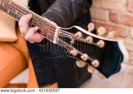 Street musician playing guitar. Selective focus on left hand. Guitar neck close up.