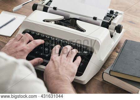 Over The Shoulder View Of Man Using A Typewriter At Wooden Table