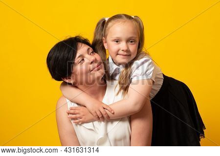 Photo Of Pretty Young Mommy Hold Arms Hugging Little Daughter Good Mood On Color Background.