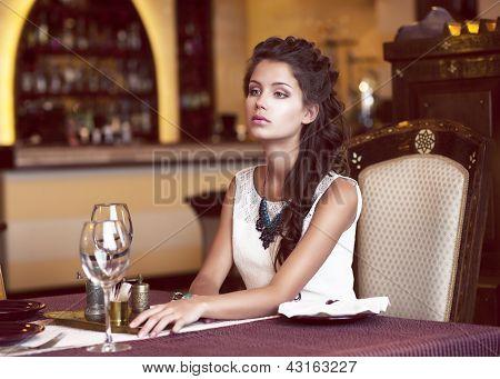Dativ. Träumende Frau wartet am dekorierten Tisch im Restaurant-Interieur