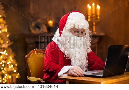 Workplace of Santa Claus. Cheerful Santa is working on the laptop while sitting at the table. Fireplace and Christmas Tree in the background. Christmas concept.