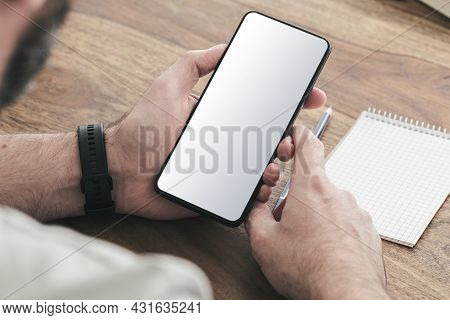 Over The Shoulder View Of Man Sitting At Wooden Table Using A Smartphone