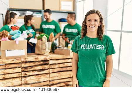 Group of young volunteers smiling happy working at charity center.