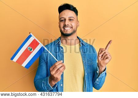 Young arab man holding costa rica flag smiling happy pointing with hand and finger to the side