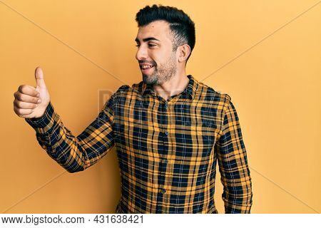 Young hispanic man wearing casual clothes looking proud, smiling doing thumbs up gesture to the side