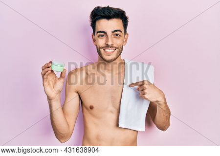 Young hispanic man shirtless wearing towel and eye bags patches pointing finger to one self smiling happy and proud