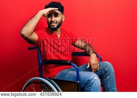 Arab man with beard sitting on wheelchair very happy and smiling looking far away with hand over head. searching concept.