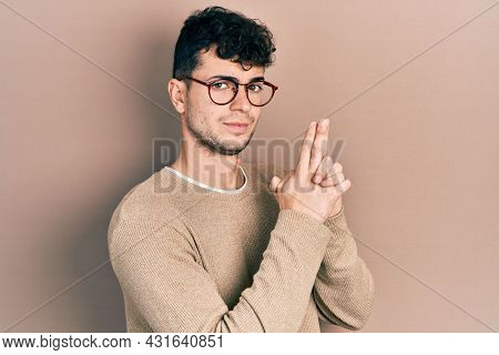 Young hispanic man wearing casual clothes and glasses holding symbolic gun with hand gesture, playing killing shooting weapons, angry face