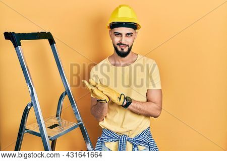 Handsome man with beard by construction stairs wearing hardhat clapping and applauding happy and joyful, smiling proud hands together